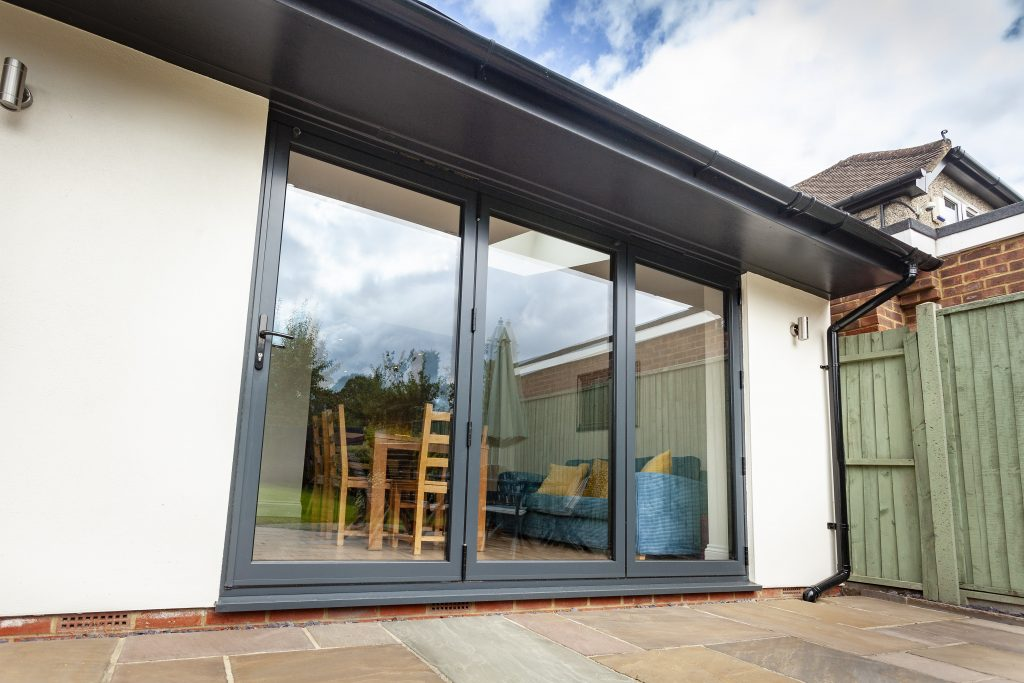 Anthracite grey bifold door on a modern white rendered extension showing patio area